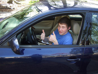 boy behind wheel of car showing two thumbs up