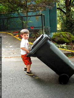 small boy dragging garbage can down driveway