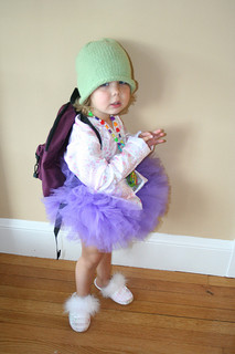 little girl in tutu with sweater, backpack, and winter hat