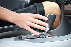 young person's hand reaching for car shifter