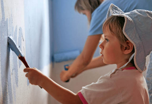 boy helping mom by painting wall