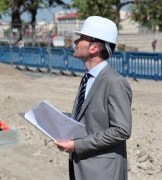 Dobrin Georgiev wearing hard hat and holding plans at construction site