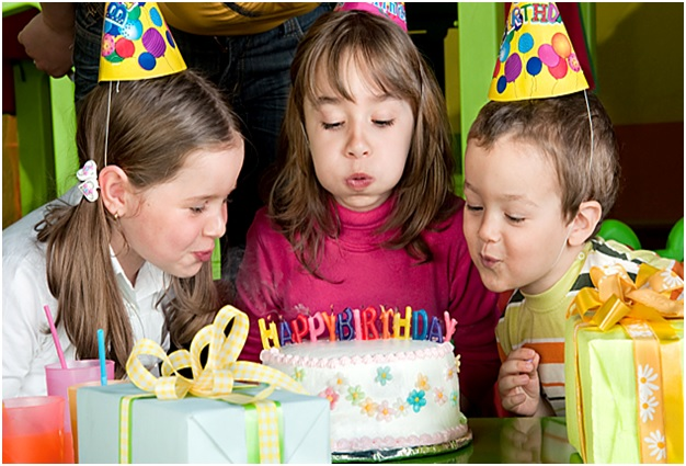 young kids blowing out candles on birthday cake