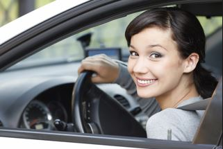 teen girl sitting in driver's seat of car