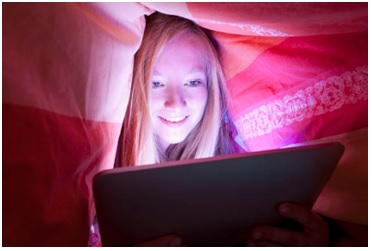 teen girl using computer under covers