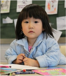little girl holding crayon, seated at table in classroom