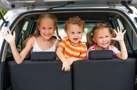 3 children sitting in back of van, waving