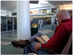 man reading book while sitting at airport