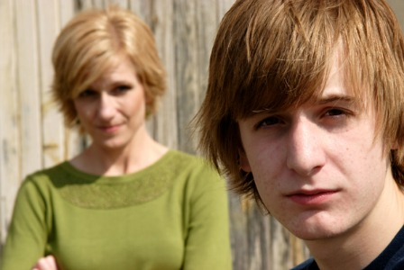 mother standing behind teen boy, both looking at camera