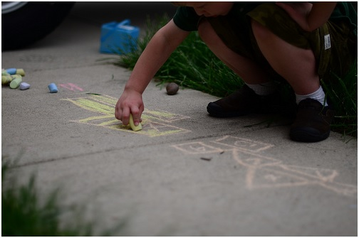 child making art on sidewalk