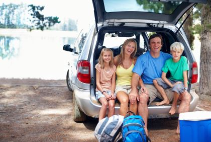 family sitting in back of car packed to travel