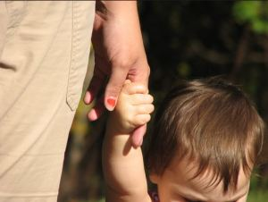 small child walking with parent, holding hands