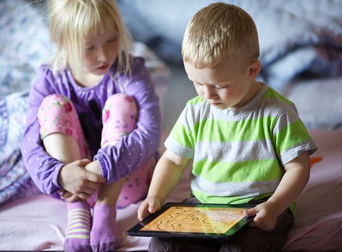 young boy and girl playing an app on a tablet