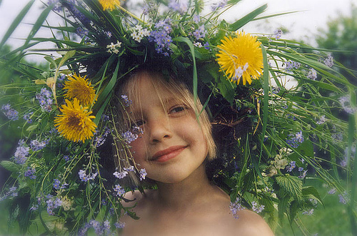 girl smiling with hat made of flowers