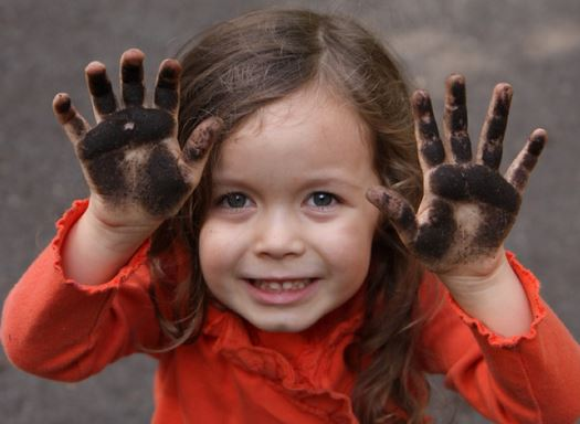 girl with muddy hands smiling at camera