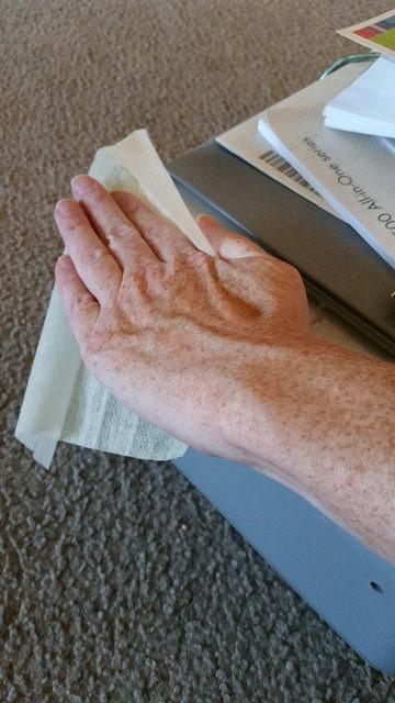 hand using Clorox dust wipe to clean printer