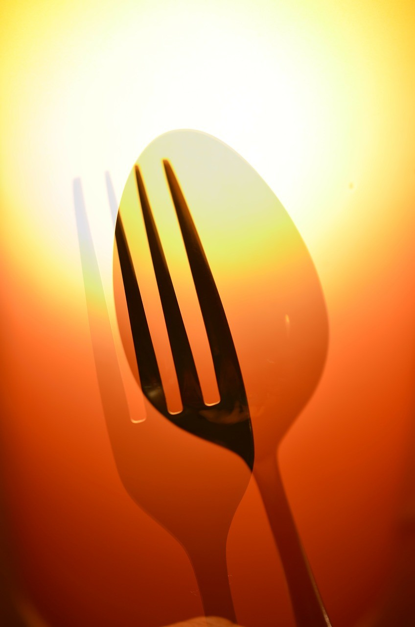 fork and spoon in front of sun