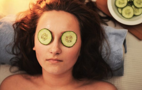 woman relaxing with cucumbers on her eyes