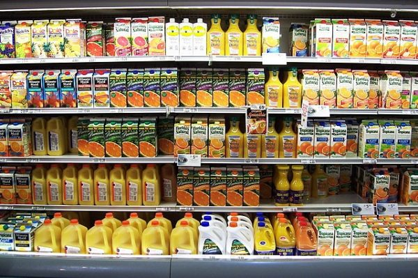 shelves of juice cartons in refrigerated section of store