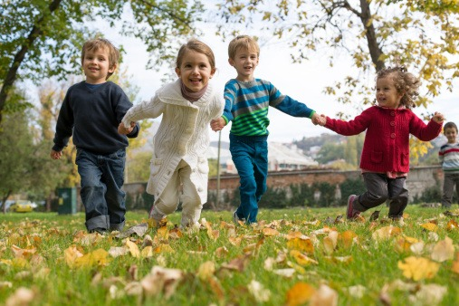 children holding hands and running in field