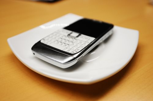 Old smartphone on white plate, with focus on the corner buttons