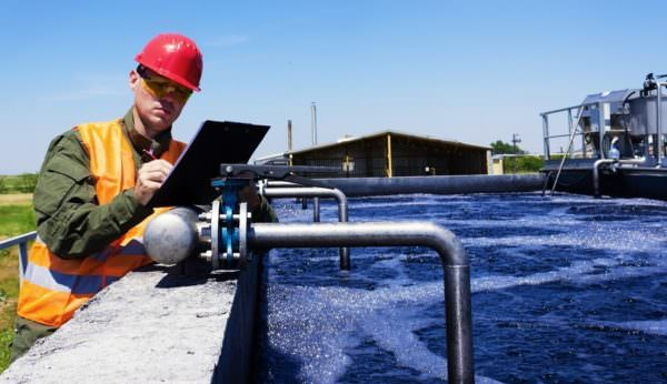 Worker inspecting valve for water filtration. Image: Adobe Stock