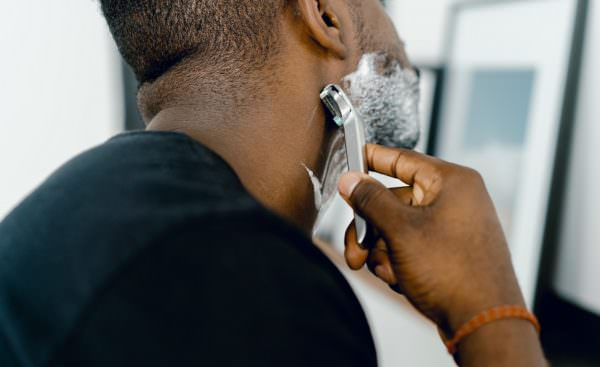 man shaving with reusable metal safety razor