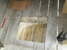 One of the holes leading through the floor at the top of the ramp.