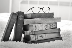 stack of old novel hardback books,eye glasses on top, on romantic love