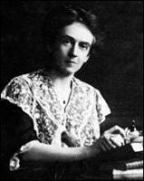 A portrait photograph of Edith Hamilton as she works on her writing, glancing at the photographer.