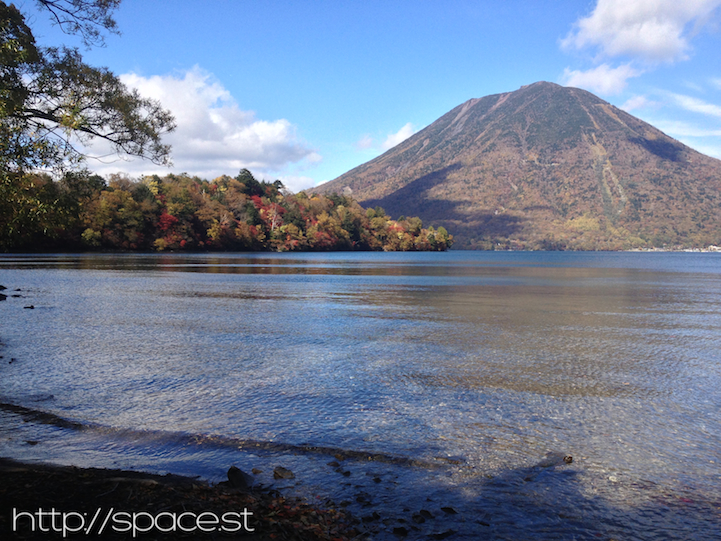 autumn leaves on Lake Chuzeji at Nujina Peninsula with Nantai Mountain in the background.