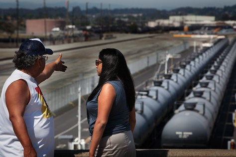 Soto and Peesapati stand near crude oil rail cars. The city of Richmond is in the background.