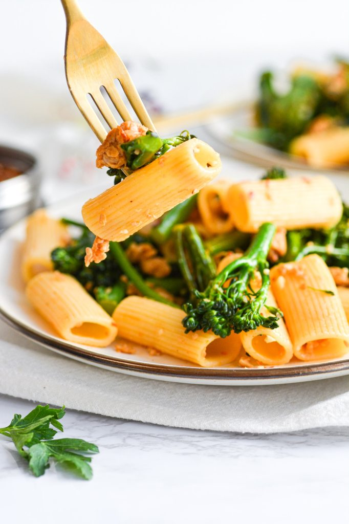 Gold fork with a bite of Rigatoni with Sausage and Broccolini on it.