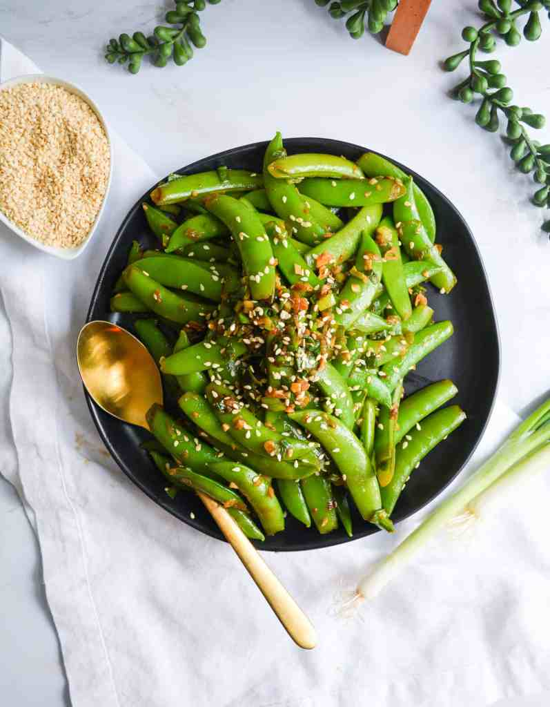 Overhead shot of snap peas on a black plate with toasted sesame seeds