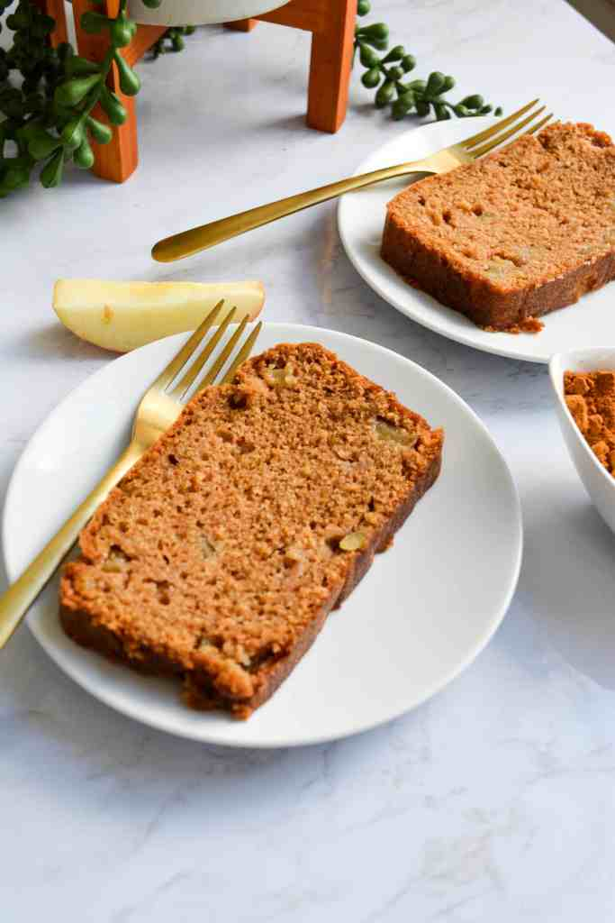 Portrait of a slice of Easy Chai Spiced Apple Loaf on a white plate