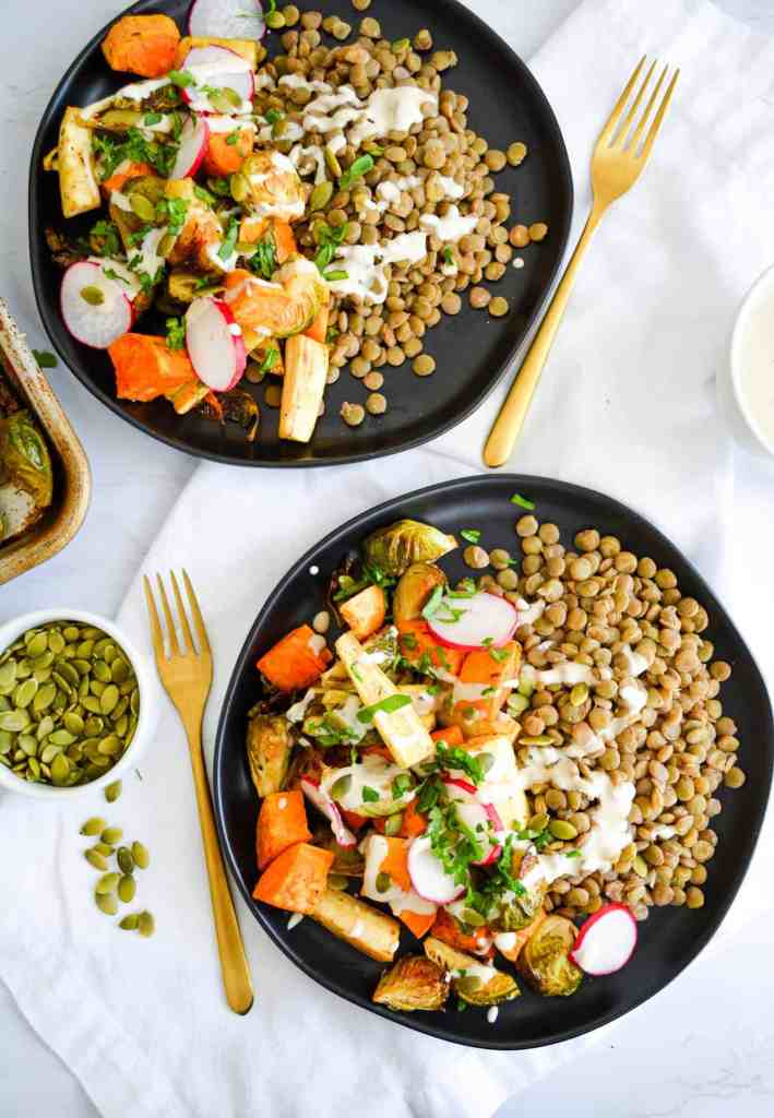 flat shot of two Easy Roasted Autumn Harvest Bowls on black plates with pepitas