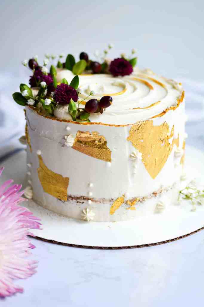 Apple cake decorated with berries, flowers and gold accents