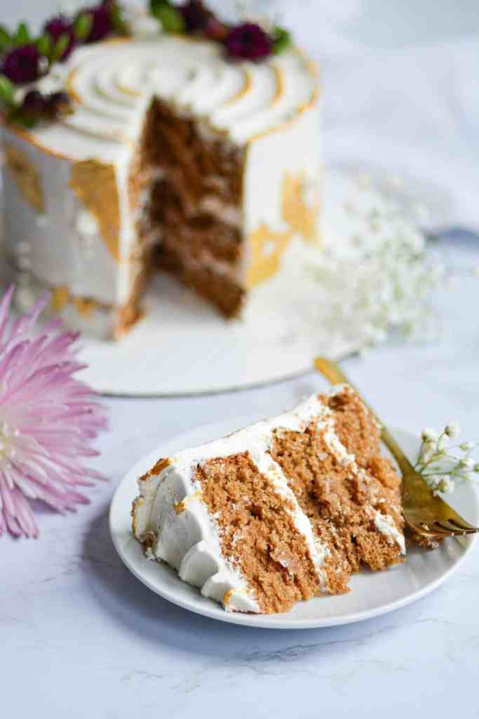 A slice of cake on a white cake with the full cake in the background
