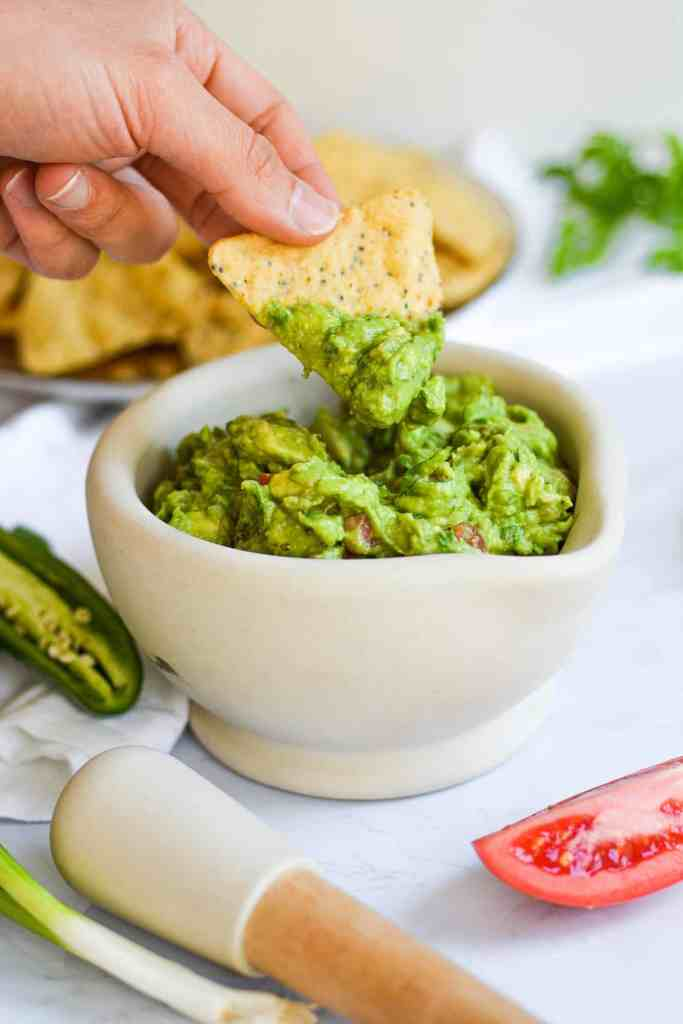 Hand holding a tortilla chip with guacamole on it