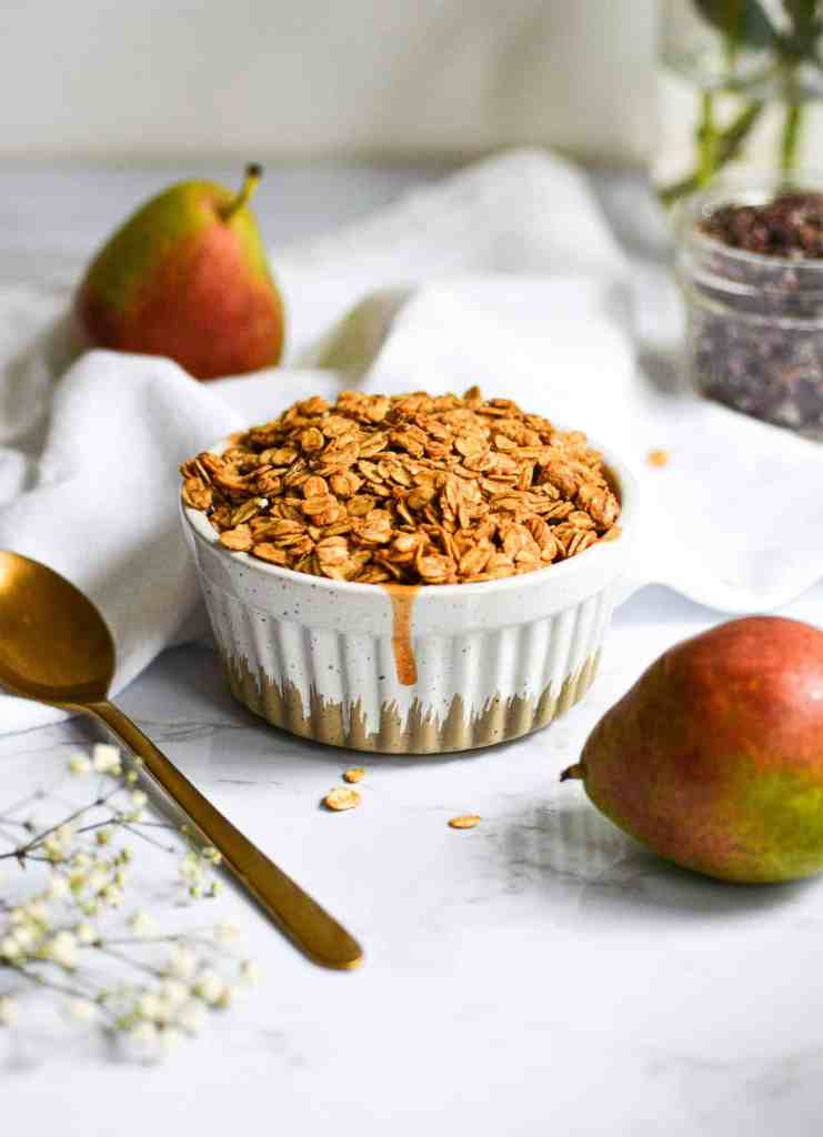 Baked pear crisp in a ramekin with small red and green pears in the background