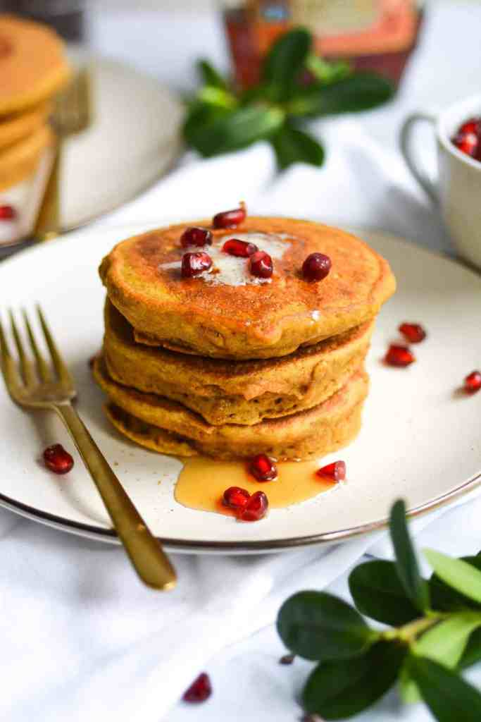 Portrait of a stack of pancakes on a plate with vegan butter, syrup and pomegranate arils