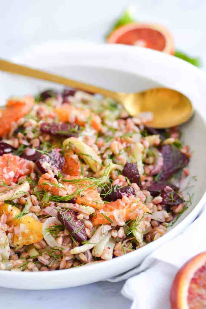 Close up of a bowl of Warm farro salad with a gold serving spoon