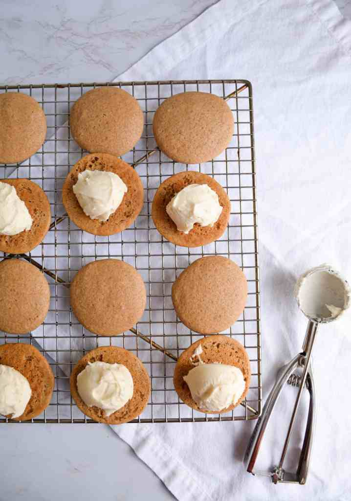 whoopie pies on a cooling rack getting sandwiched with vanilla buttercream