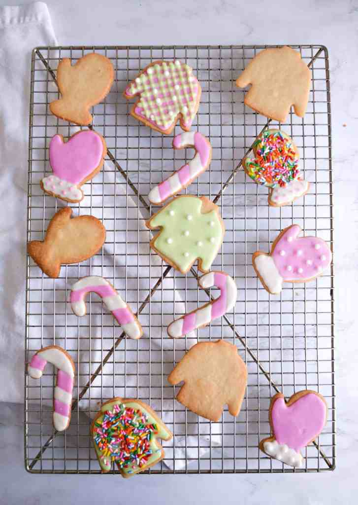 Decorated Vegan Cut-Out Holiday Cookies on a wire cooling rack over a white background