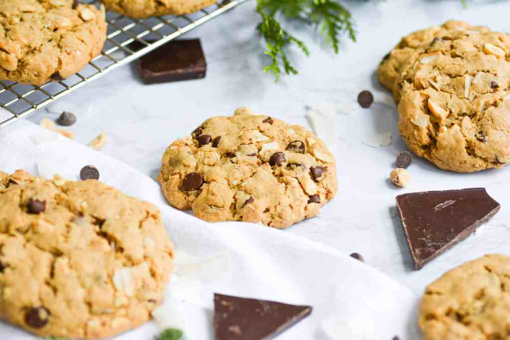 oatmeal chocolate chocolate chip cookies on a white board with pieces of chocolate scattered around