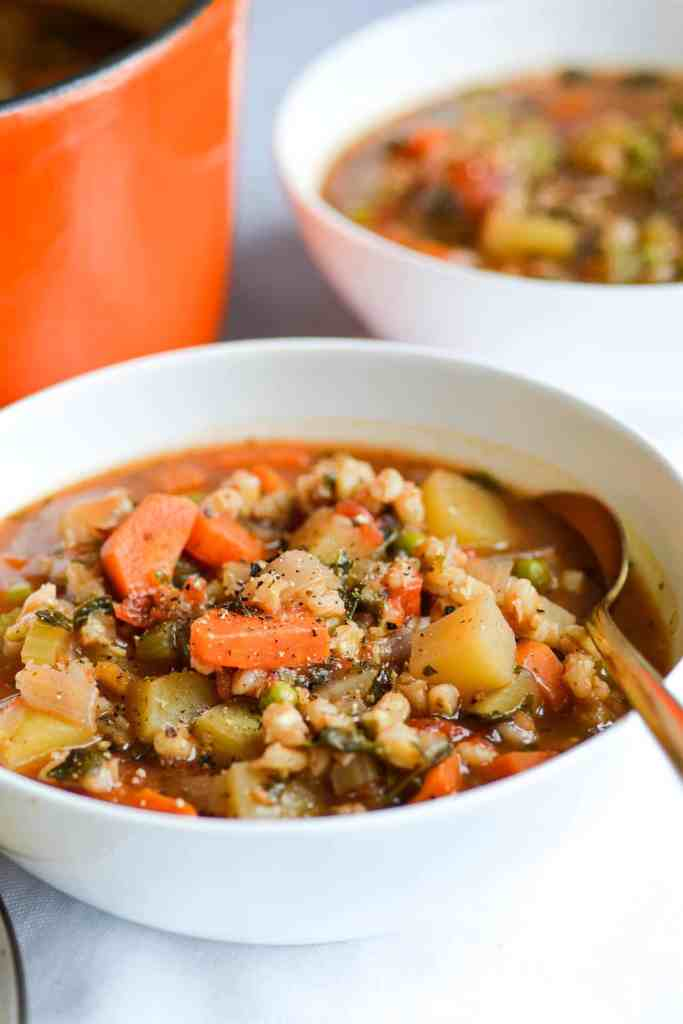 Two bowls of Vegetable and Barley Stew next to an orange dutch oven