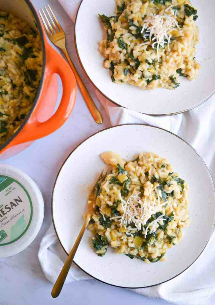 overhear shot of two plates of vegan leek and kale risotto on a marble board