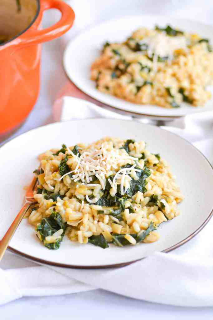 two plates of vegan leek and kale risotto next to an orange dutch oven