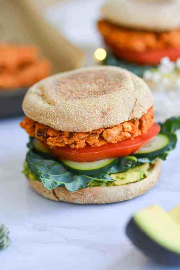 close up of a buffalo chickpea veggie burger on an eglish muffin with avocado, tomato and kale