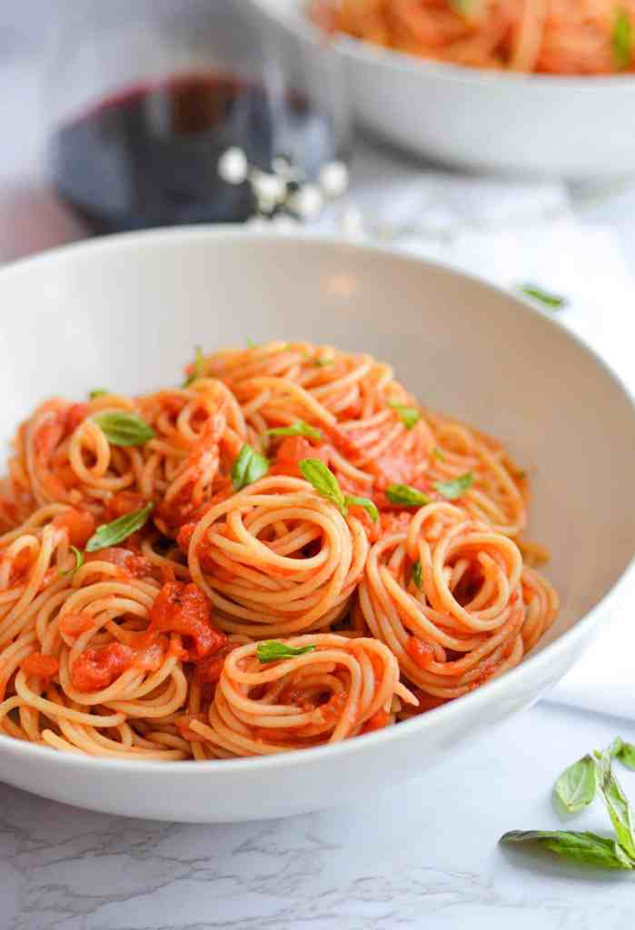 Lanscape of spaghetti with tomato sauce in a white bowl topped with basil